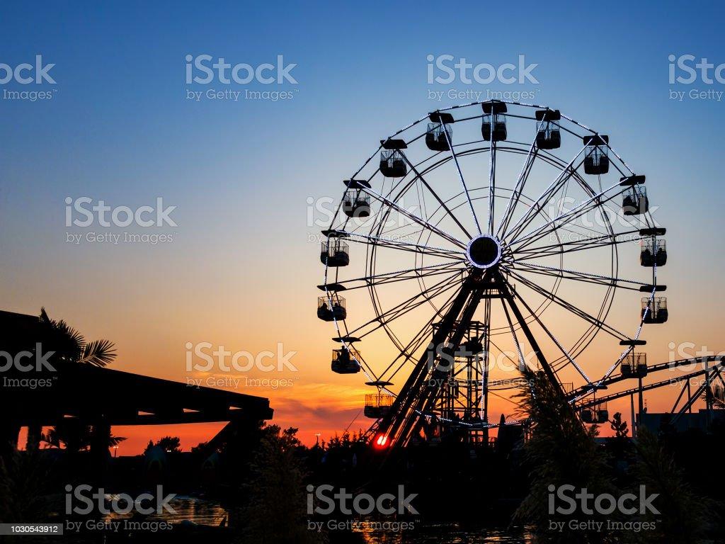 Riesenrad im Sonnenuntergang.  Riesenrad mit Kabinen – Foto
