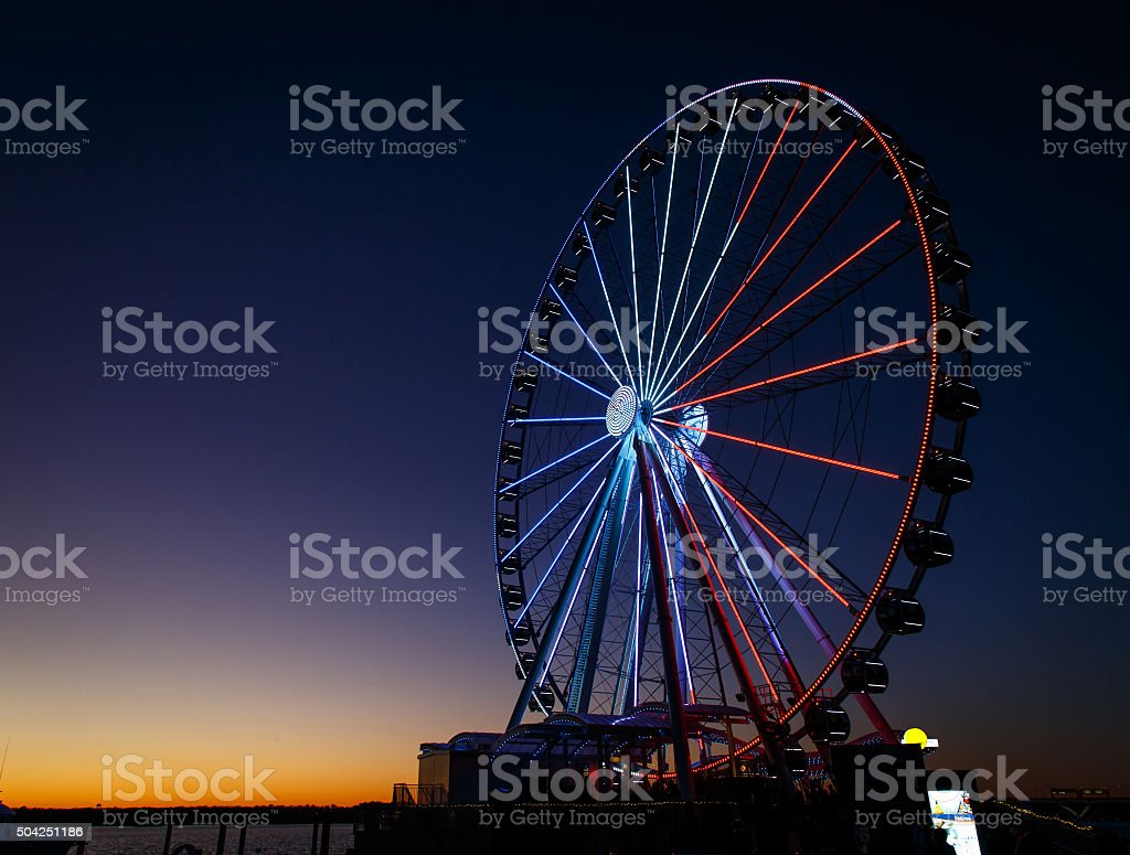 ferris wheel lit up red, white and blue stock photo
