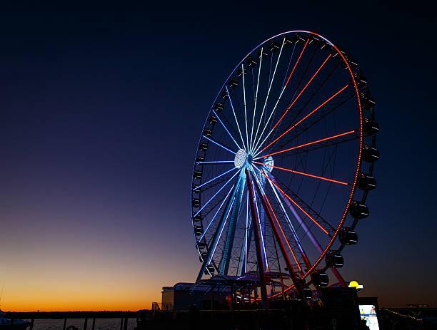 ferris wheel lit up red, white and blue - haven stockfoto's en -beelden