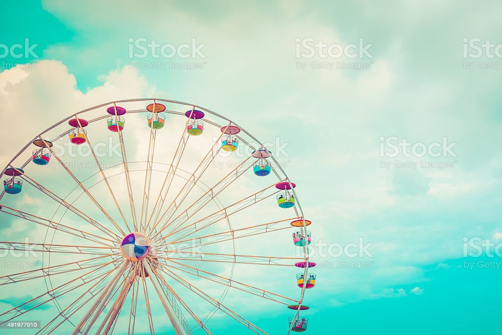 Ferris wheel on cloudy sky background vintage color stock photo