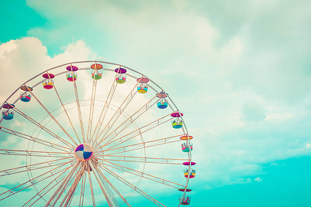 Ferris wheel on cloudy sky background vintage color Ferris wheel on cloudy sky background vintage color ferris wheel stock pictures, royalty-free photos & images