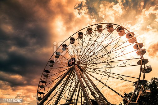 Color image depicting the ferris wheel on the banks of lake Geneva in Geneva, Switzerland. No one is riding in the cabins, and there is the red and white of the Swiss national flag displayed in the center of the ferris wheel. The big wheel is offset by a beautiful sunset and cloudscape. Room for copy space.