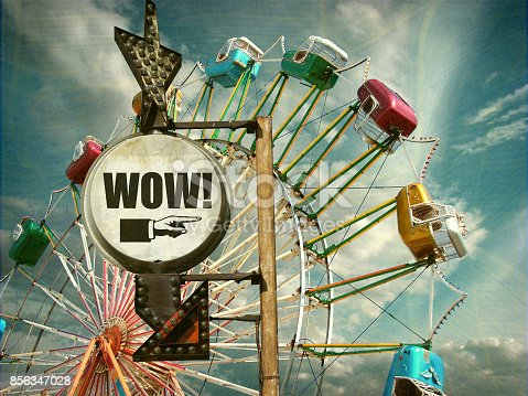 aged and worn vintage photo of ferris wheel and wow sign
