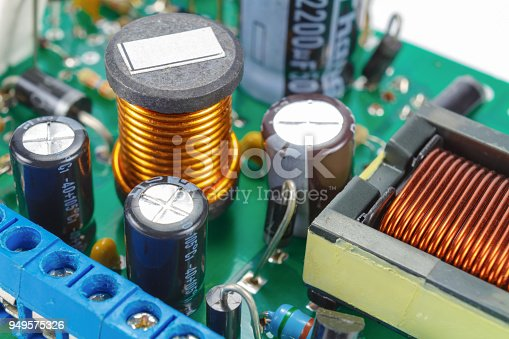 istock Ferrite choke and electrolytic capacitors mounted on the circuit Board 949575326