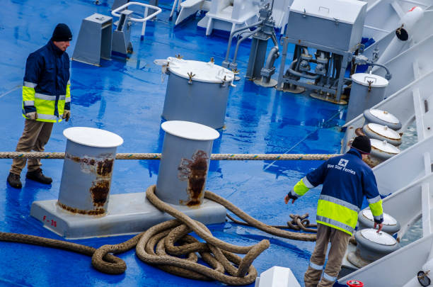 Ferry boat crew working on the deck of the boat untying the ropes for the departure. stock photo