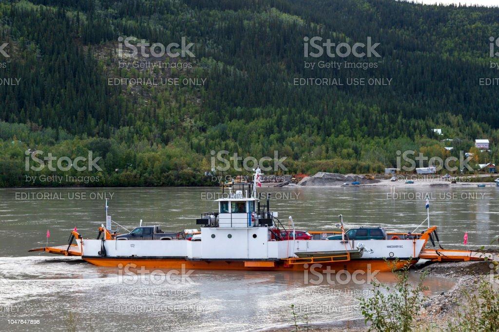 Ferry barco cruzando el río de Yukon en Dawson, para llegar a la cima de la carretera del mundo, la mayoría notherly entre Yukon y Alaska. - foto de stock