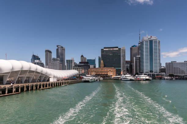 Ferry Building and Auckland skyline under blue sky. stock photo