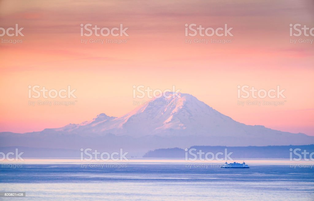 A ferry crossing the Puget Sound at sunrise with Mount Rainier in the background, Washington, USA stock photo