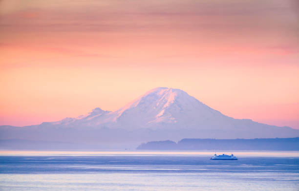 A ferry crossing the Puget Sound at sunrise with Mount Rainier in the background, Washington, USA A ferry crossing the Puget Sound at sunrise with Mount Rainier in the background, Washington, USA puget sound stock pictures, royalty-free photos & images