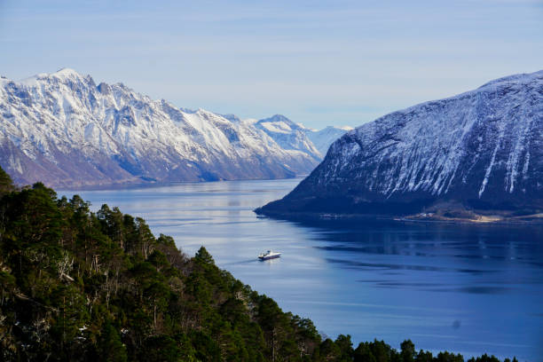 Ferry is crossing the fjord. Dramatic landscape at the Hjorundfjord, Norway stock photo