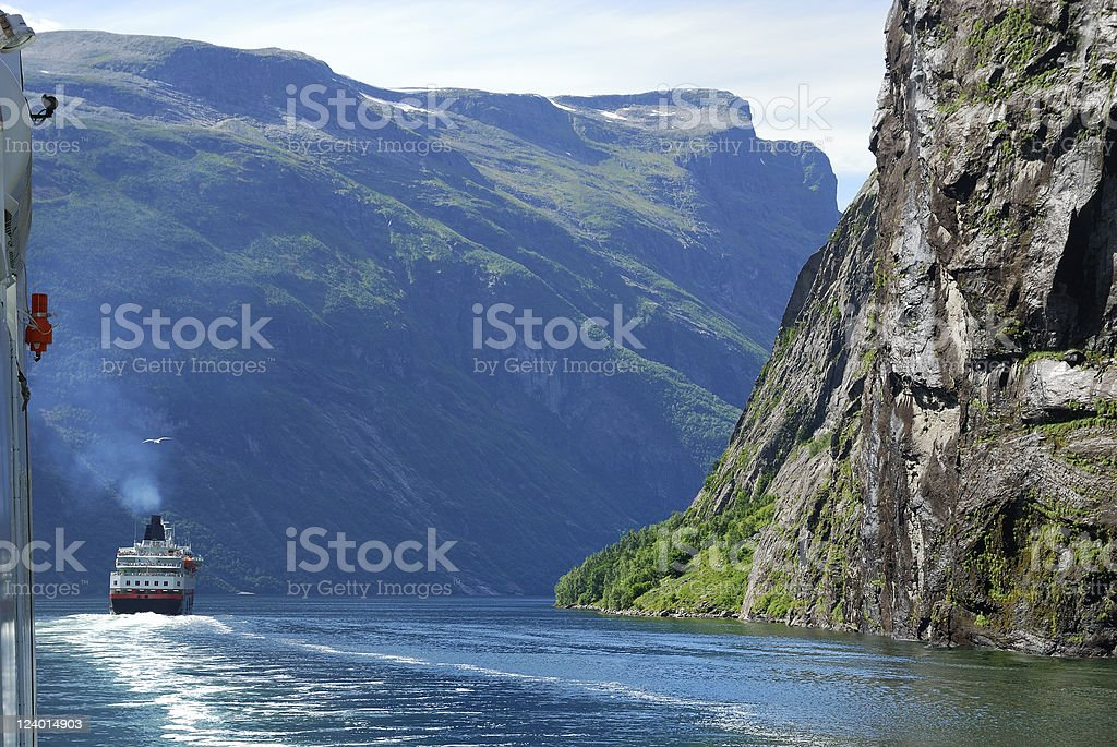 Ferry on blue water of Norwegian fjord. stock photo