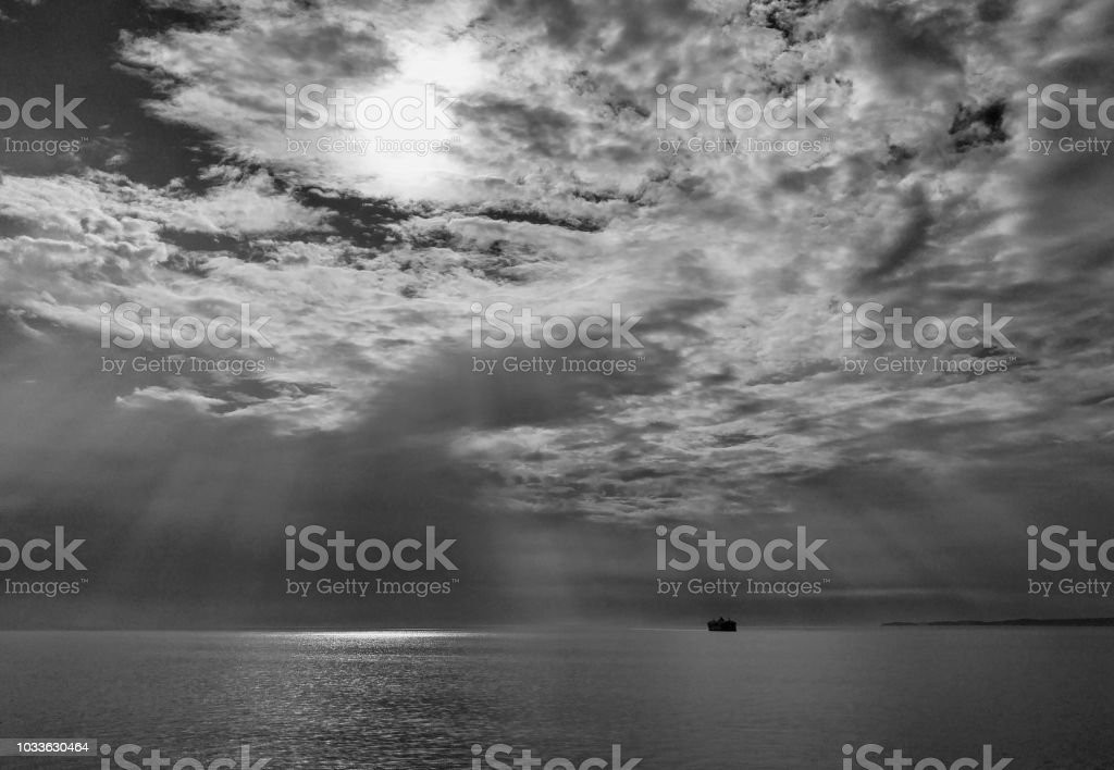 A ferry passes quietly on a cloudy day on the ocean stock photo