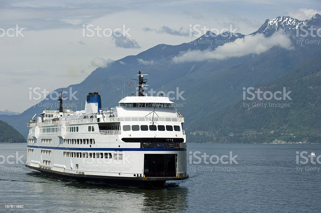 A ferry sailing through a waterway surrounded by hills stock photo