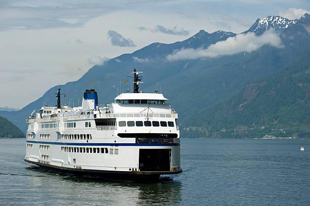 a ferry sailing through a waterway surrounded by hills - veerboot stockfoto's en -beelden