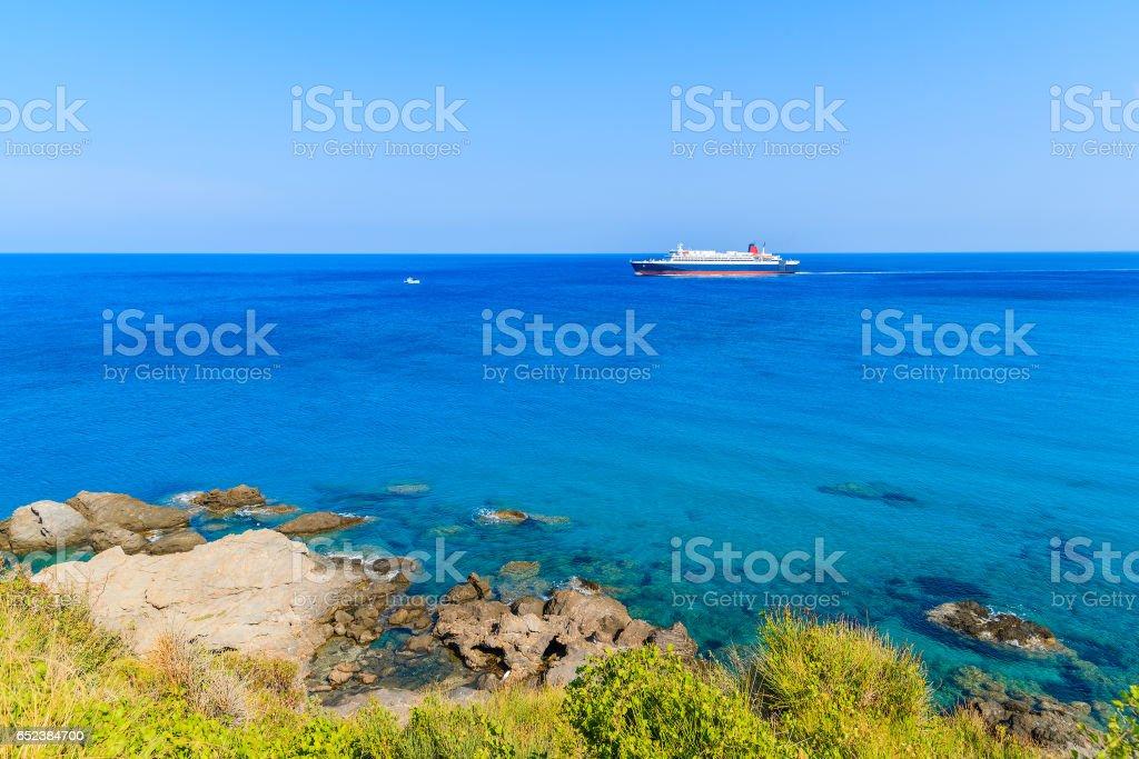 Ferry ship on blue sea sailing along coast of Samos island, Greece. stock photo