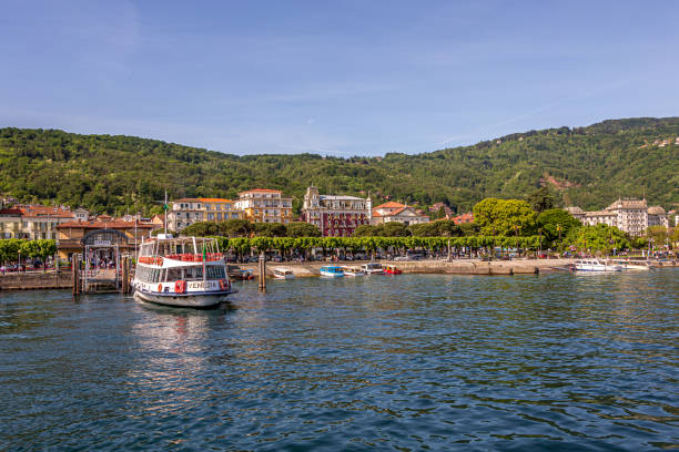 A ferry sits in dock awaiting passangers on a bright summers day with the beauty of town and local boats along the shoreline stock photo