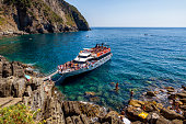 31 july 2017 - Riomaggiore, Italy:  Overcrowded regular ferry boat near Riomaggiore in Cinque Terre, Italy in July 2018. Boat is popular tourist attraction as it provides different perspective on Cinque Terre cities