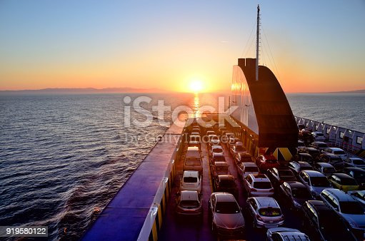 Ferry with cars on the sea at sunset