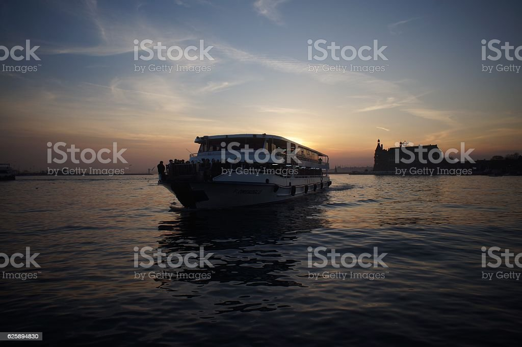 Ferry with people on sunset stock photo