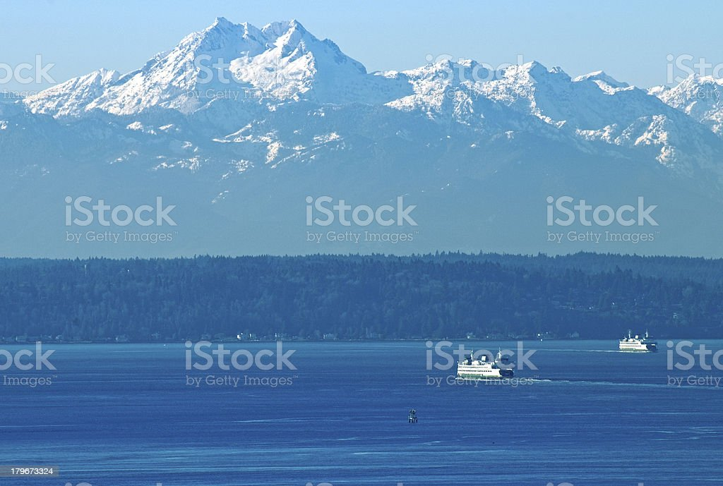 Ferryboats crossing Elliott Bay under Olympic Mountains in Seattle WA stock photo
