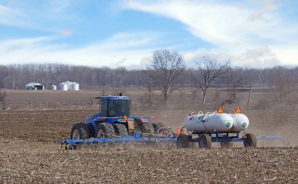 Fertilizing a Farm Field Farm tractor pulling anhydrous ammonia tanks fertilizing farmland anhydrous stock pictures, royalty-free photos & images