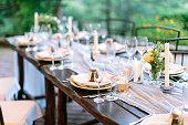 フェスト、ディナー、伝統概念。銀製品、料理と見事な透明ガラス、花と八角形の形で興味深いホルダーにキャンドルでお祝いを提供しています長いオーク材テーブル