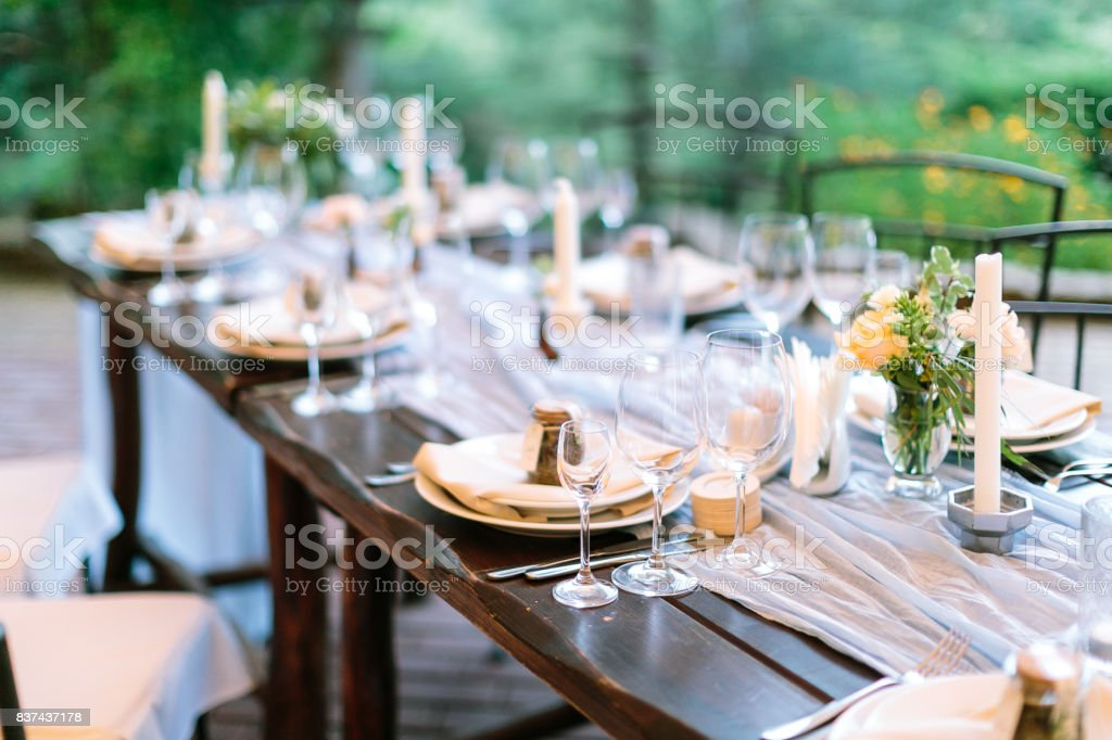 fest, dinner, tradition concept. long oaken table served for celebration with silverware, dishes and transparent dazzling glasses, flowers and candles in interesting holders in form of octagonal stock photo