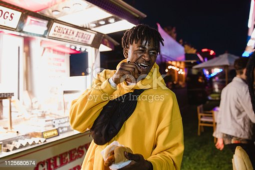 Young man is laughing with friends while eating a hot dog from a food van at a festival.