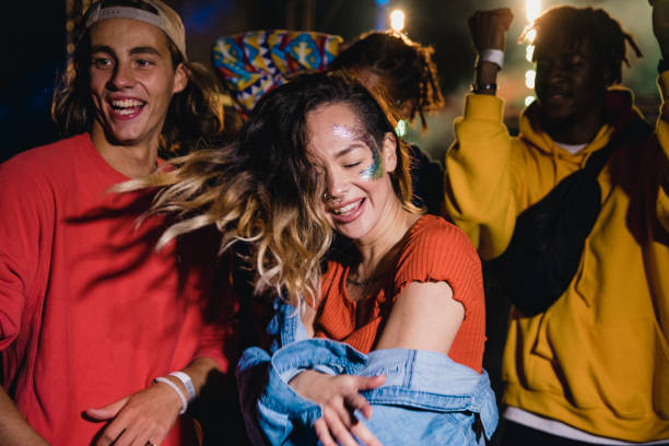 Festival Boogie Young woman is dancing wildly at a music festival with her friends. college fair stock pictures, royalty-free photos & images