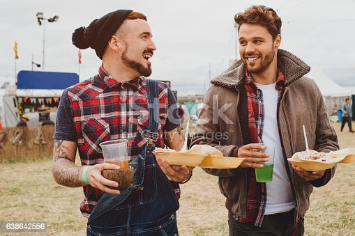 Two men are walking together at a music festival. They have kebabs and alcoholic drinks in their hands and they are talking as they walk.