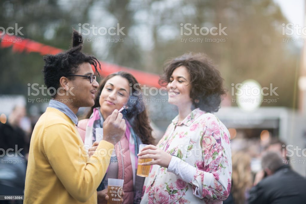 Festival : friends having a drink together and smoking a cigaret stock photo