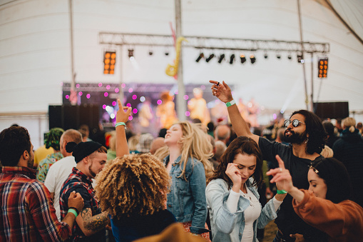 Group of friends dancing together in a marquee at an outdoor music festival.