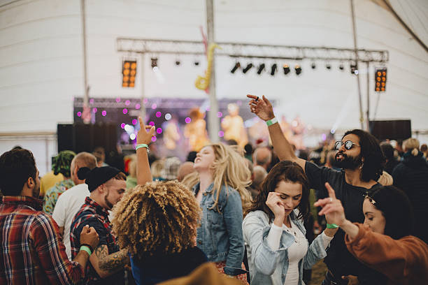 Festival fun Group of friends dancing together in a marquee at an outdoor music festival. entertainment tent stock pictures, royalty-free photos & images