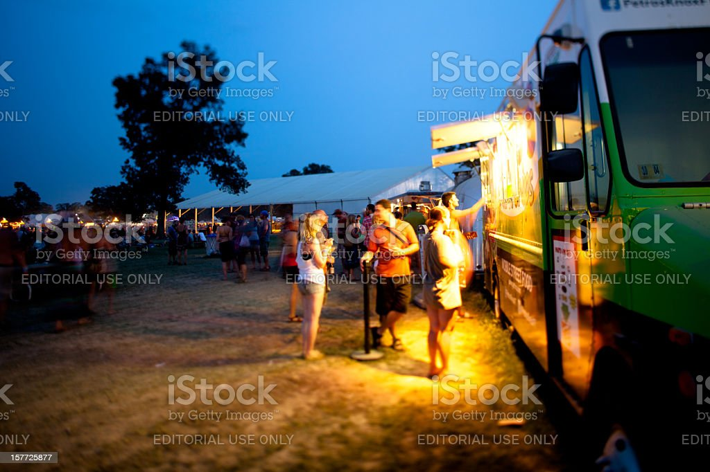 Festival goers getting dinner from a food truck stock photo