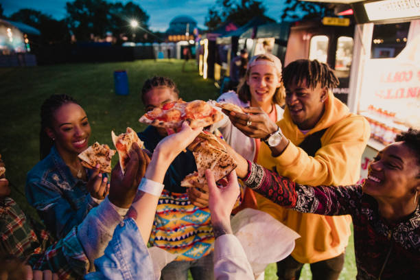 Festival Goers Sharing Pizza A young group of friends sharing and enjoying pizza at a music festival, making a celebratory toast with slices. food festival stock pictures, royalty-free photos & images
