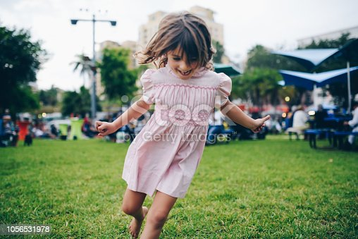 Adorable little girl in a vintage pink smocked dress, runs around. Nostalgic, retro styled image. Peace, love, and childhood. Full of energy, vitality and a cool festival feeling
