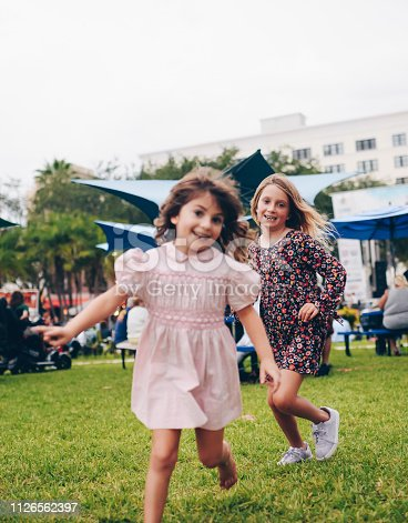 Adorable little girls in a vintage pink smocked dress and flowered jumper, run around. Nostalgic, retro styled image. Peace, love, and childhood. Full of energy, vitality and a cool festival feeling