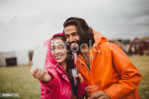 Young couple are at a music festival in rainy weather. They are wearing colourful rain macs and are using a smartphone to take a selfie of them together.