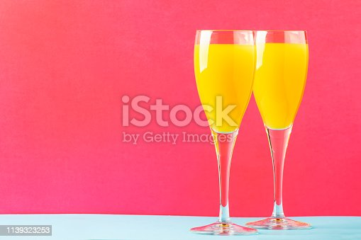 Festive alcohol cocktail mimosa with orange juice and cold dry champagne or sparkling wine in glasses, pink trendy background, place for text, selective focus