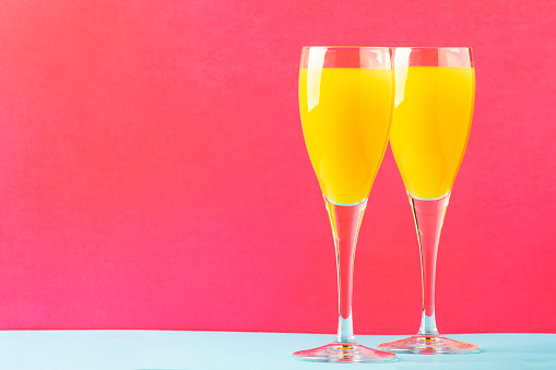 Festive alcohol cocktail mimosa with orange juice and cold dry champagne or sparkling wine in glasses