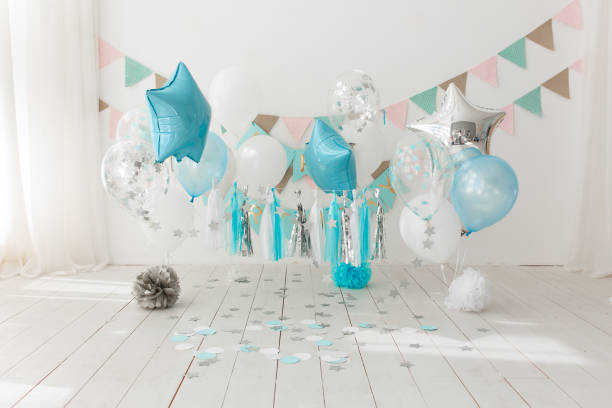 Festive background decoration for birthday celebration with gourmet cake and blue balloons in studio, cake smash first year concept stock photo