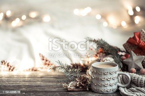 Festive background with Cup on wooden background with lights and festive decor. Coziness and comfort at home. The concept of the new year holiday.