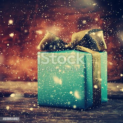 493890050istockphoto Festive Box on Wooden Christmas Background with Snowfall 493884692