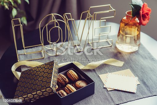 Festive box with chocolate macaroons cakes, rose flower in vase, postcard and wire word Love on gray napkin. Cozy gift idea for lover. Hygge Valentine's day concept. Romantic mood in noir nordic style.