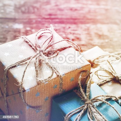 493890050istockphoto Festive Boxes in  Brown Paper with Linen Cord on Wooden 493981280