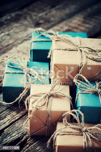 493890050istockphoto Festive Boxes with Cord. Color Gifts on Wooden Background 495727306