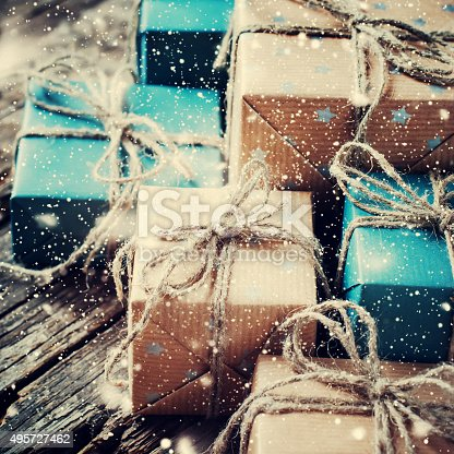 493890050istockphoto Festive Boxes with Linen Cord. Drawn Snowfall. Toned 495727462