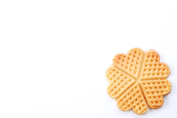 Festive breakfast composition with homemade waffles in the shape of heart for valentine's day. Plain freshly baked homemade heart shaped Belgium waffles isolated on white background. European baked pastry sweets. Copy space, close up, top view, flat lay. St. Valentine's Day breakfast concept. waffle stock pictures, royalty-free photos & images