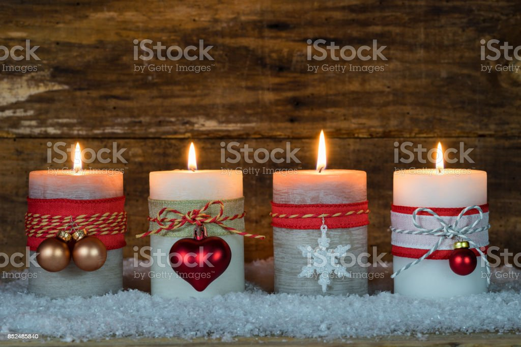 Festive burning Christmas candles with ornaments stock photo