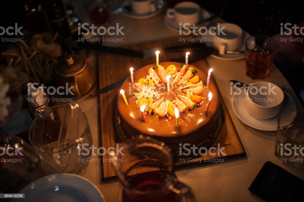 Festive Cake With The Burning Candles On A Table Happy Birthday